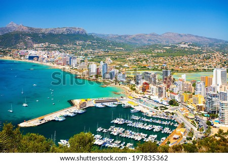 Panorama of the city on the seafront with people relaxing on the beach and yachts in the bay (Spain, Calpe) - stock photo