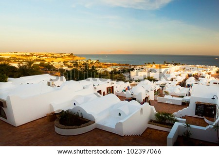 Panorama of the coast of Egypt to the white city (Sharm el Sheikh) in a morning sunrise - stock photo