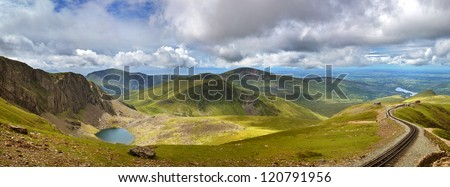 Panorama of the mountains of Snowdonia looking from Mount Snowdon, with a vintage steam train climbing from the town of LLanberis to the summit. - stock photo