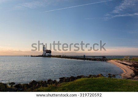 Panorama of the of Lighthouse of Marken, called â??Paard van Markenâ?, translated as â??Horse of Markenâ? in the morning sun on the shore of the Ijsselmeer in the North of Holland. - stock photo