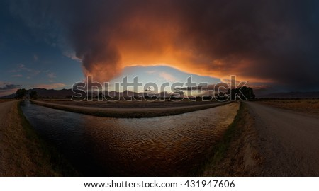 panorama of the Owens Valley at sunset with an irrigation canal and the Sierra Nevada Mountains and dramatic clouds - stock photo