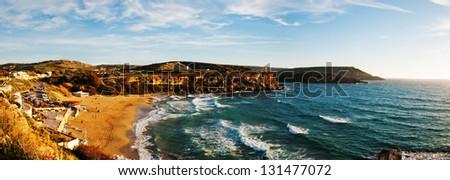 Panorama of the popular sandy beach of Golden Sand Bay, Malta awash in evening sunlight - stock photo