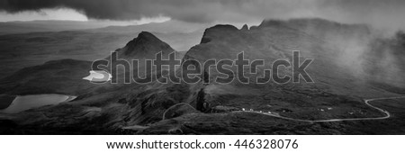 Panorama of the Quiraing, Isle of Skye, Scotland from above with highland mountain road and overcast, cloudy sky over the hills and mountain lakes in dramatic and contrasty black and white - stock photo