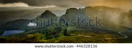 Panorama of the Quiraing, Isle of Skye, Scotland from above with highland mountain road and overcast, cloudy sky over the hills and mountain lakes in abstract, desaturated color with yellow cloud - stock photo