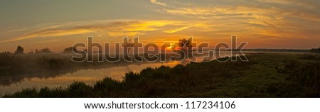 Panorama of the river with fog when the sun is below the horizon. - stock photo