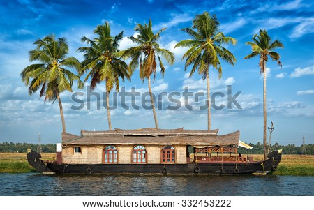 Panorama of tourist houseboat on Kerala backwaters with palms in background. Kerala, India - stock photo