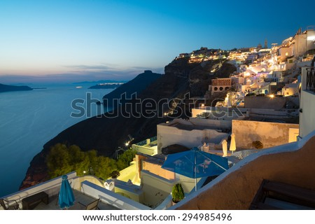 Panorama of traditional terraced houses in Fira, Santorini at dawn - stock photo