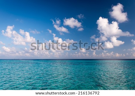 Panorama of  tropical island with turquoise lagoon. Bright blue sky with clouds low over the ocean. Summer joyful day - stock photo