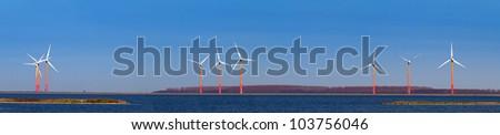 Panorama of wind mills on shore - stock photo