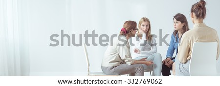Panorama of women sitting in circle during session with psychologist - stock photo