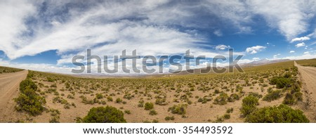Panorama of 4x4 track in desert in the mountains of Eduardo Avaroa Andean Fauna National Reserve with cloudy blue sky, Bolivia - stock photo
