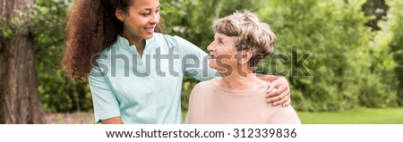 Panorama of young female afroamerican caregiver supporting elderly woman - stock photo