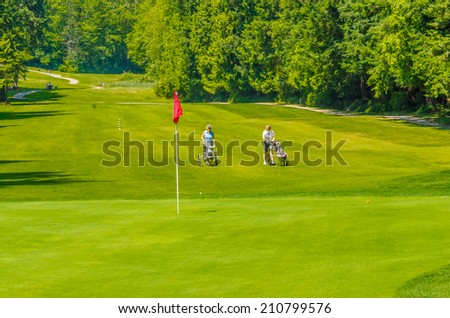 Panorama, outlook at the beautiful golf course with red flag in a sunny day. Canada, Vancouver. - stock photo