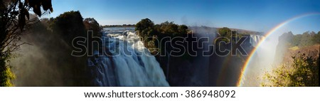 Panorama photo of  Victoria Falls or Mosi-oa-Tunya, waterfall on Zambezi river in high flow from Devil's Cataract  in late evening light with rising spray and white water due to long time exposure. - stock photo