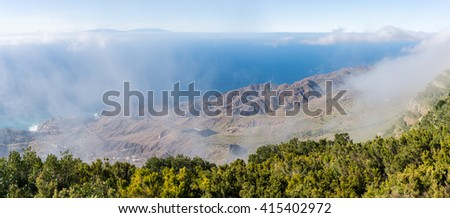 Panorama picture from the overlook Mirador de Alojera to the canyon Barranco del Mono with the village Alojera. Trade winds with scattered clouds comes from the north into the valley - stock photo