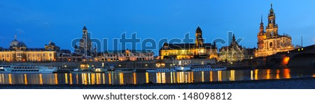 panorama skyline of dresden by the elbe river, germany, in the blue hour, buildings with artificial lighting
