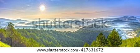 Panorama sunrise over hill with the sun radiating golden rays pierced the hills with pine trees covered with morning dew beautiful ray beam forming to welcome the new day so simple in Da lat, Vietnam - stock photo