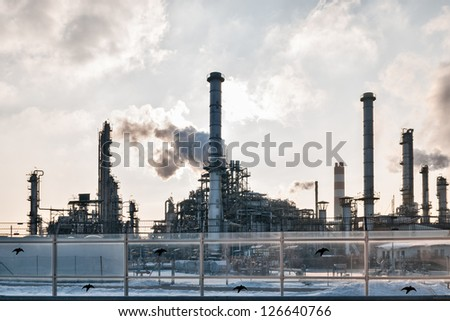 panorama view of an oil refinery with smoking chimneys in winter against blue sky