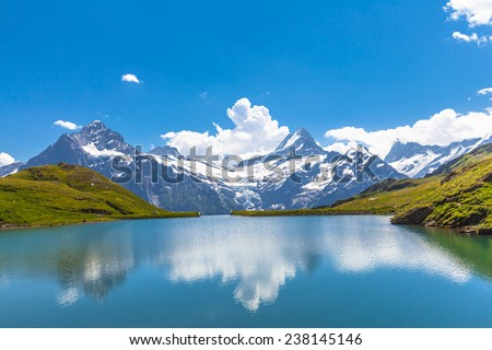 Panorama view of Bachalpsee and the snow peaks with glacier of swiss alps - stock photo