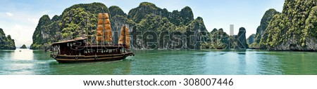 panorama view on sea gulf Halong bay with ship surrounded with high mountains, direct rocks with green trees and blue sky and clouds at sunny day,Southeast Asia, Ha Long Bay, Vietnam