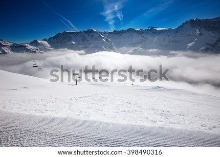 Panorama view to Swiss Alps and chair lift in Elm ski resort, Switzerland. Elm is famous ski resort with 40 km prepared ski slopes, 4 km tobogganing slopes and children arena.  - stock photo