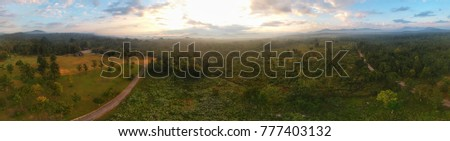 Panoramic aerial view of beautiful green tropical forest with mountains and majestic blue sky and clouds. Camping site at Maeping National Park, Lamphun, Thailand.