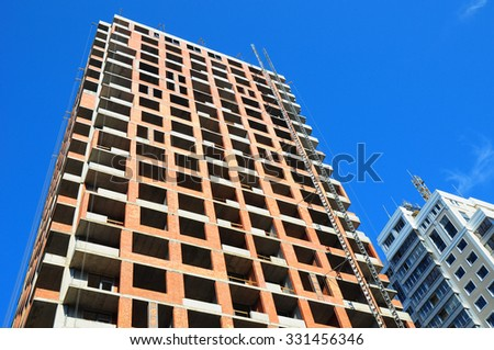 Panoramic and perspective wide angle view to high-rise building under construction exterior. The site building construction facade walls against blue sky. - stock photo