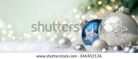 Panoramic Christmas background with nice shiny baubles on snow and defocused lights in the background, with light green copy space - stock photo