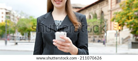 Panoramic close up portrait view of an attractive smiling young professional businesswoman using smartphone technology in a classic city, outdoors. (Business, People, Technology) - stock photo