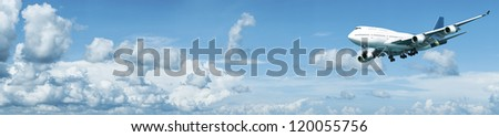 Panoramic composition of a jumbo jet in a blue cloudy sky - stock photo