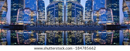 Panoramic evening city view with its reflection in the water of the river. - stock photo