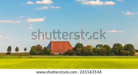 Panoramic image of a Dutch farm with wind turbines in the province of Friesland - stock photo