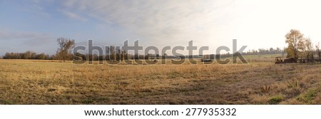 Panoramic image of large farm in the glow of the afternoon sunlight with a softness of color in the sky - stock photo