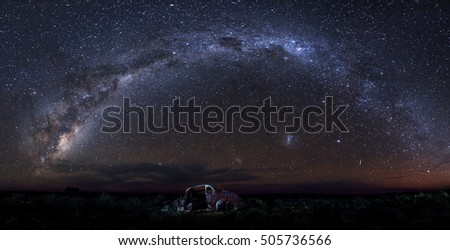 panoramic image of milky way and old car wreck