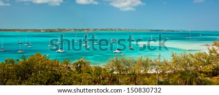 panoramic image of the harbour, or anchorage, in the bahamas near George Town in the Exumas.  Sand bar with small boat dock is off to the right and copy space is available in the clear blue sky - stock photo