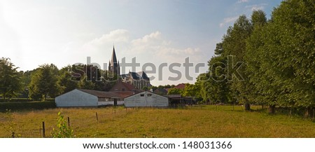 Panoramic landscape of meadow with church and trees and blue cloudy sky. Thorn. Zuid Limburg. The Netherlands. - stock photo