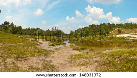 Panoramic landscape of park with lake and trees with blue cloudy sky. Zuid Limburg. The Netherlands. - stock photo