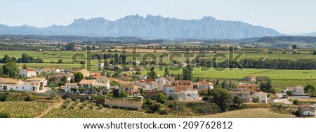 Panoramic landscape with a small village surrounded by vineyards and Montserrat multi-peaked mountain at background, Barcelona, Catalonia, Spain. - stock photo