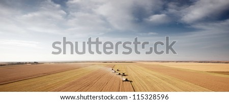 Panoramic landscape with four combines in a field on the open prairie - stock photo