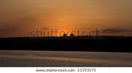 panoramic landscape with the glow of a sunset above the river - stock photo