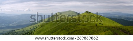 Panoramic mountain landscape with cloudy stormy sky and green sunny foreground grass with a lone backpacker - stock photo
