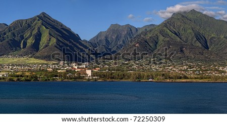 Panoramic mountains tower over Kahului, the island of Maui's largest community. - stock photo