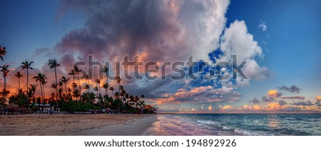 Panoramic ocean bay sunset with spectacular clouds, palm trees, and azure waters - stock photo
