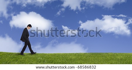 Panoramic of a businessman walking on the grass thinking about his life - stock photo