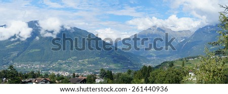 Panoramic of the valley basin of Merano in South Tyrol, Italy; sunny day in summer,  blue sky and peaks in clouds, mountains and valleys, villages in the Meran Country/Mountain and valleys - stock photo