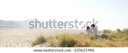 Panoramic of young tourist couple sitting together in the distance on a white sand beach with dunes on a sunny day on holiday, outdoors. Travel and vacation lifestyle, nature living spacious exterior. - stock photo