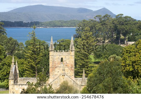 Panoramic overview of World Heritage Site Port Arthur Convict Settlement in Tasmania, Australia, with damaged church and harbour in blurred background of park, copy space. - stock photo