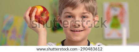 Panoramic photo of smiling boy with red apple - stock photo