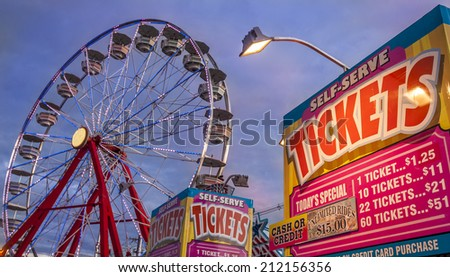 Panoramic photo of ticket sale booth in a theme park with a ferris weheel on the background at sunset. - stock photo