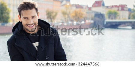 Panoramic photo with handsome smiling man in coat